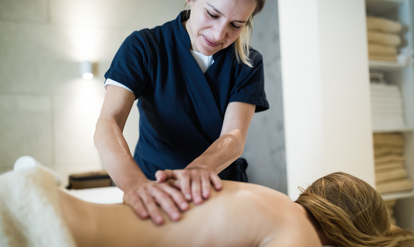 massage therapist smiling during work